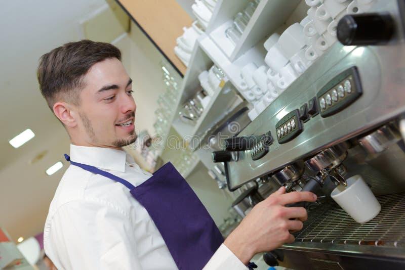 Uśmiechnięty kelner robi filiżanki kawie przy sklep z kawą zdjęcia royalty free