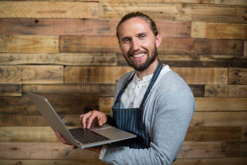 Uśmiechnięty kelner używa laptop przeciw drewnianej ścianie zdjęcia stock