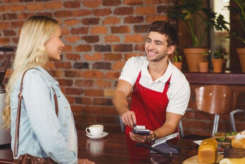 Uśmiechnięty kelner używa wałkowego terminal fotografia royalty free