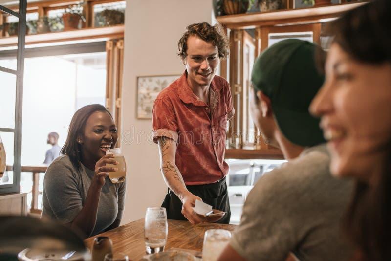 Uśmiechnięty kelner wręcza czeka stół klienci zdjęcie stock