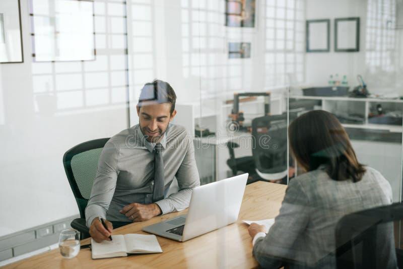 Uśmiechnięty kierownik bierze notatki podczas gdy prowadzący biurowego wywiad fotografia stock