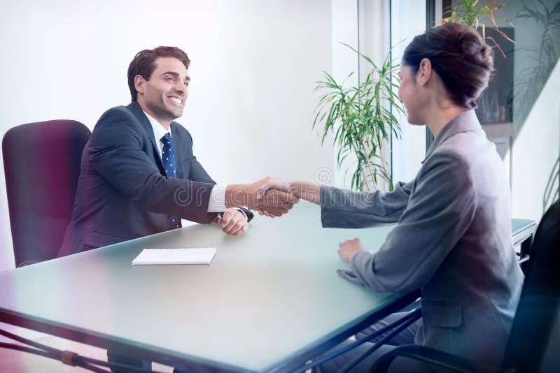 Uśmiechnięty kierownik przeprowadza wywiad dobrej przyglądającej wnioskodawcy obraz stock