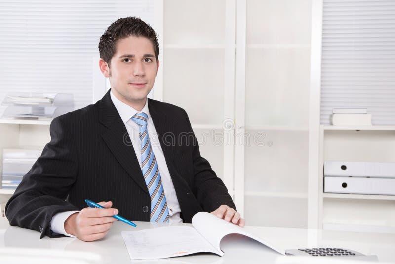 Uśmiechnięty kierownik w kostiumu i krawata obsiadaniu przy biurem. zdjęcia royalty free