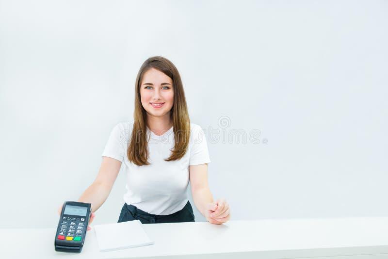 Uśmiechnięty kierownika lub sprzedawcy mienia płatniczy terminal przy recepcyjnym biurkiem Contactless zapłata z nfc technologią  zdjęcia royalty free
