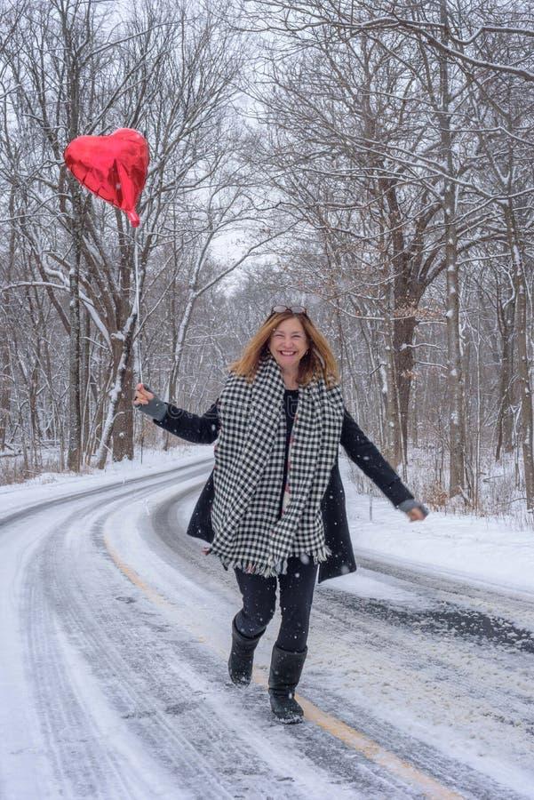 uśmiechnięty kobieta bieg w śniegu trzyma czerwonego serce kształtował balon obraz royalty free