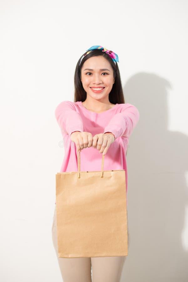 Uśmiechnięty kobieta chwyta torba na zakupy, odizolowywający na bielu obrazy stock