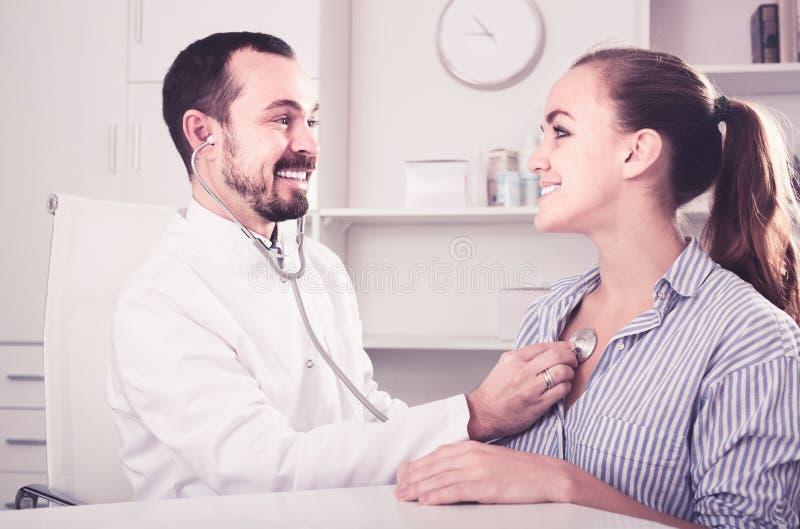 Uśmiechnięty kobieta pacjent z samiec lekarką zdjęcie stock