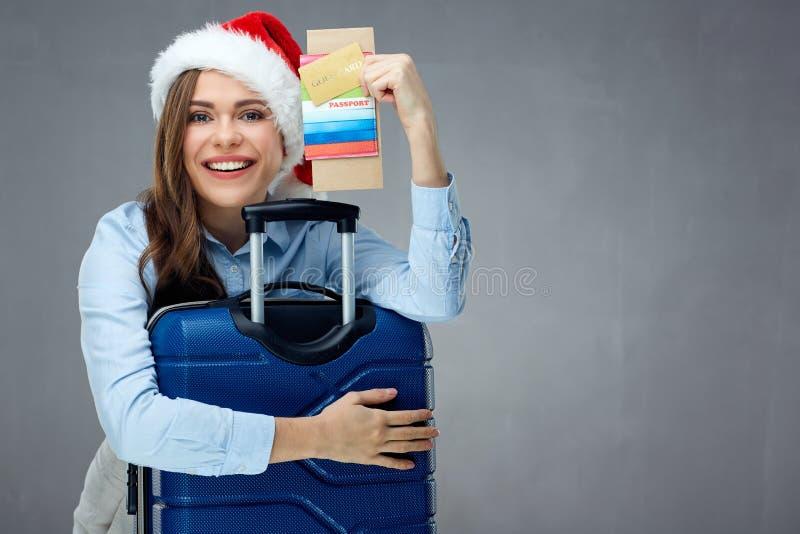 Uśmiechnięty kobieta podróżnik jest ubranym bożego narodzenia mienia kapeluszowego paszport, t zdjęcie royalty free