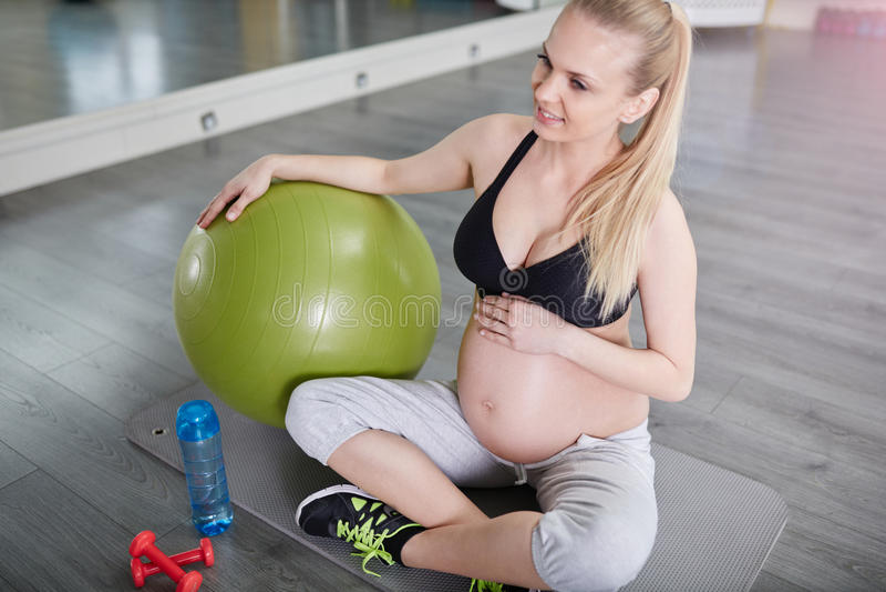 Uśmiechnięty kobieta w ciąży obsiadanie na gym macie z pilates balowymi obraz stock