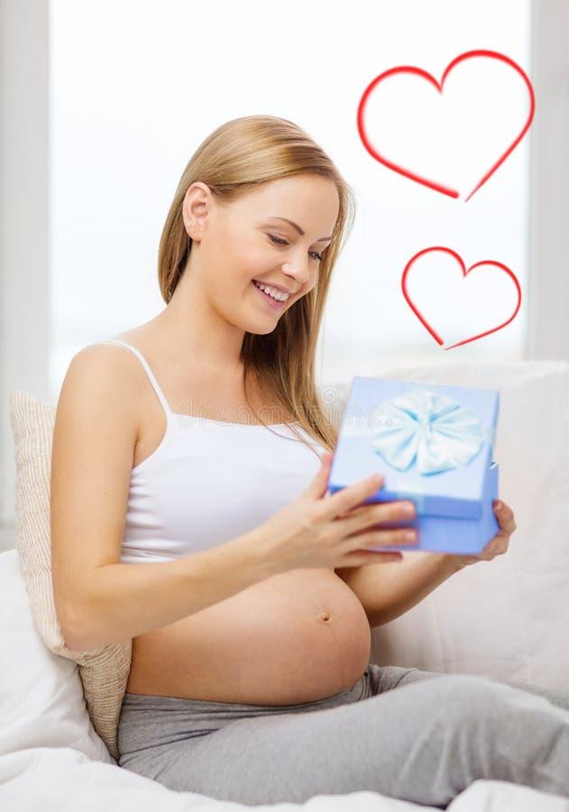 Uśmiechnięty kobieta w ciąży otwarcia prezenta pudełko obraz royalty free