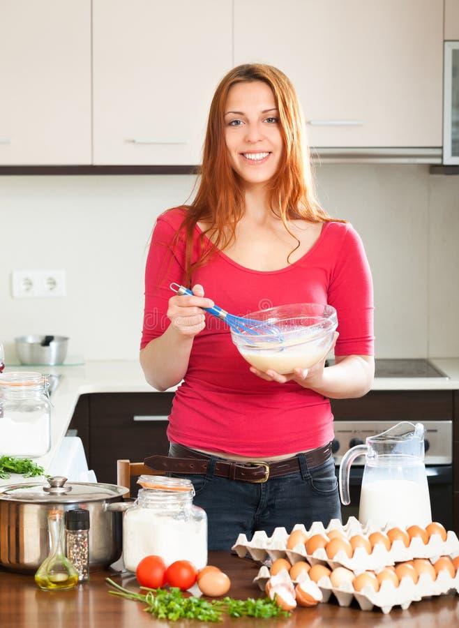 Uśmiechnięty kobiety biczowania ciasto w łęku zdjęcie royalty free