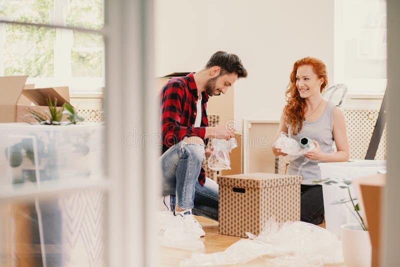Uśmiechnięty kobiety i mężczyzna kocowanie faszeruje podczas gdy poruszający od domu out zdjęcie stock