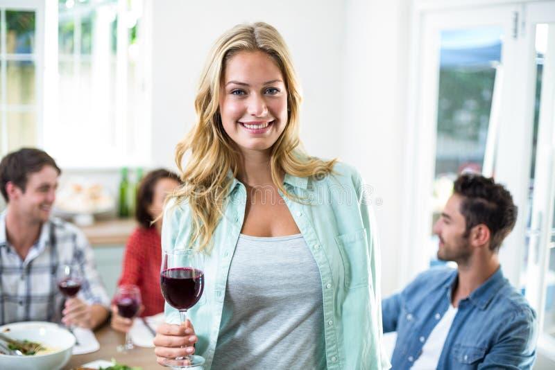 Uśmiechnięty kobiety mienia czerwonego wina szkło z przyjaciółmi fotografia stock