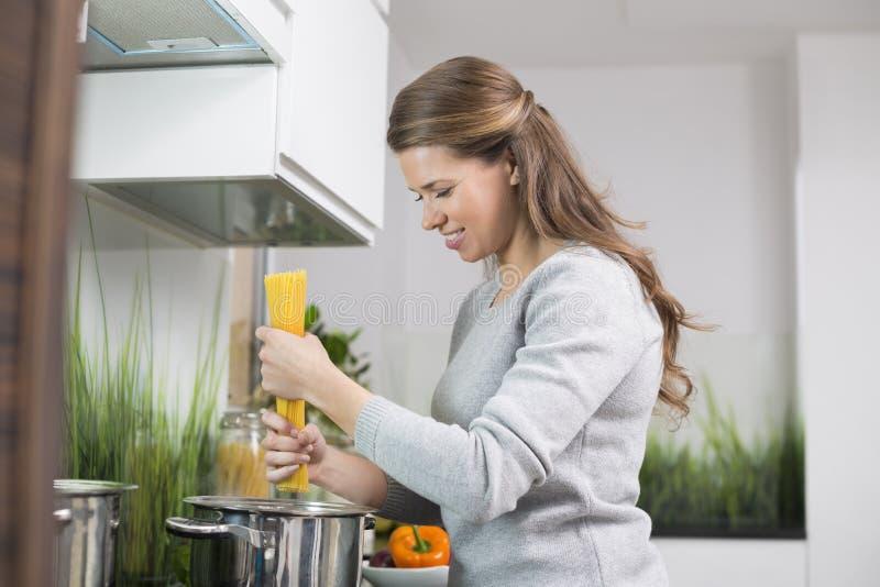 Uśmiechnięty kobiety narządzania spaghetti w kuchni obraz stock