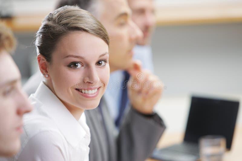 Uśmiechnięty kobiety obsiadanie przy biznesowym spotkaniem z kolegami fotografia royalty free