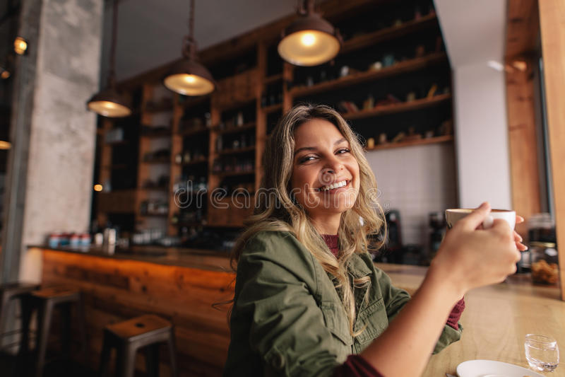 Uśmiechnięty kobiety obsiadanie przy kawiarnią z filiżanką kawy obrazy stock