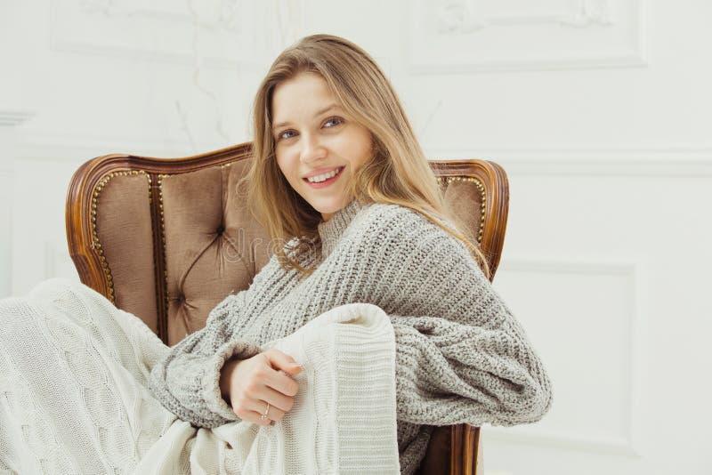 Uśmiechnięty kobiety obsiadanie w rocznika krześle, kolana zakrywający koc obraz stock