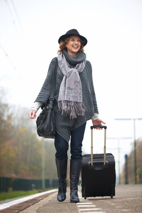 Uśmiechnięty kobiety odprowadzenie na dworzec platformie obraz stock