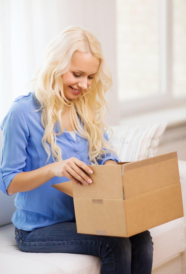 Uśmiechnięty kobiety otwarcia karton w domu fotografia stock