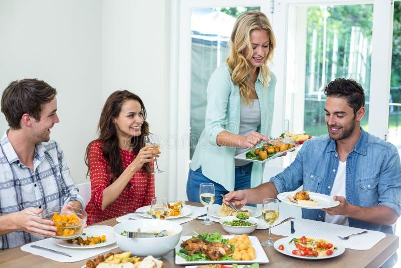 Uśmiechnięty kobiety porci jedzenie przyjaciele zdjęcie stock