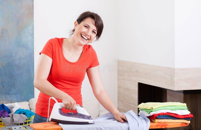 Uśmiechnięty kobiety prasowanie odziewa zdjęcie stock