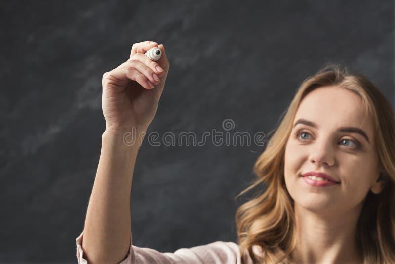 Uśmiechnięty kobiety writing coś w powietrzu z markierem obraz stock
