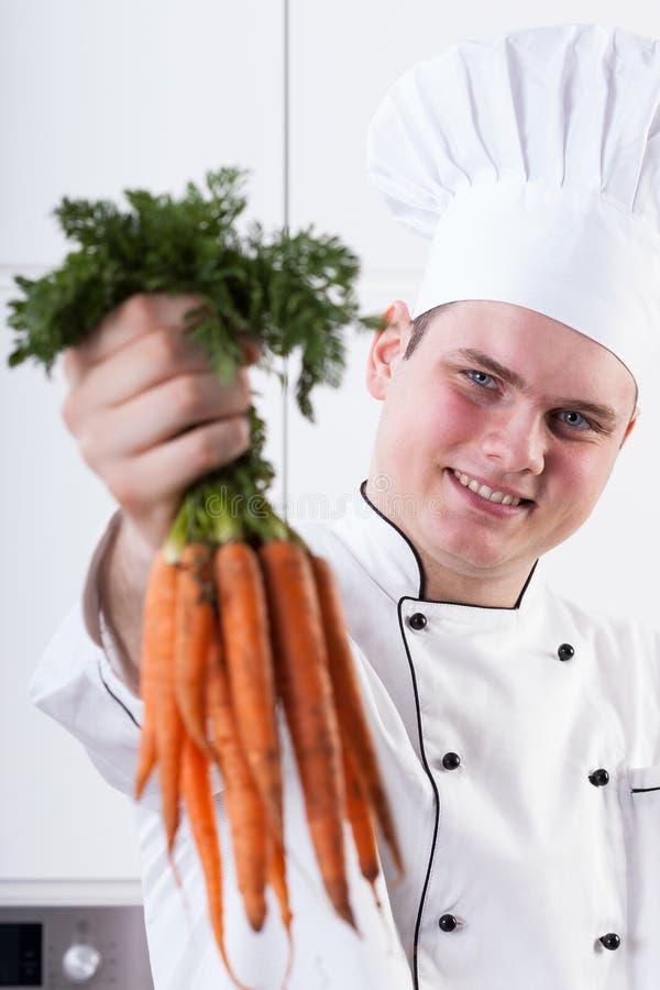 Uśmiechnięty kucharz z marchewkami obraz royalty free
