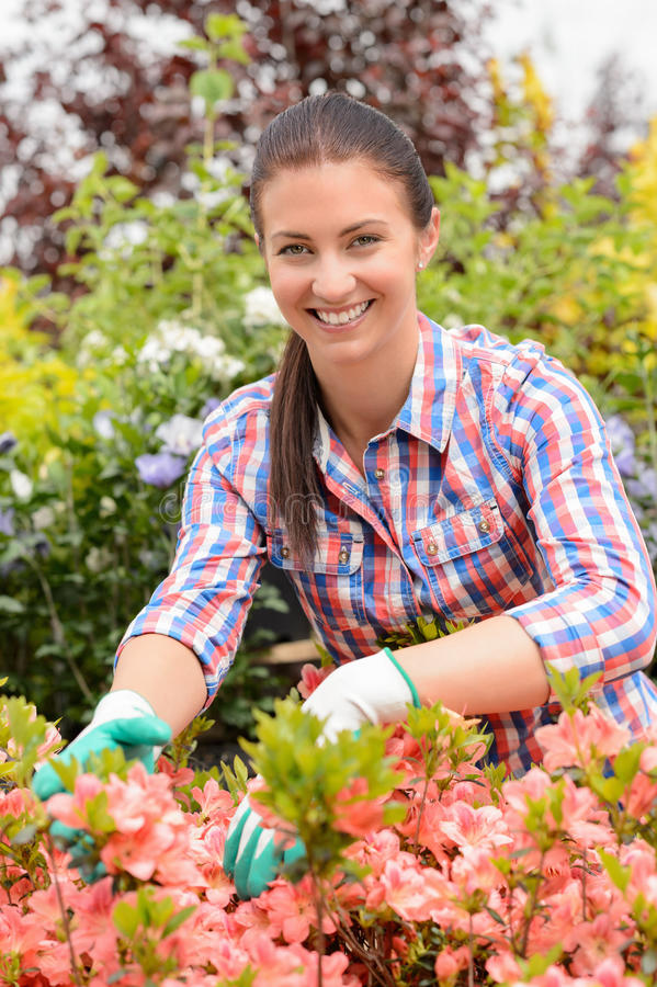 Uśmiechnięty kwiaciarni ułożenie kwitnie w ogrodowym centrum zdjęcie stock
