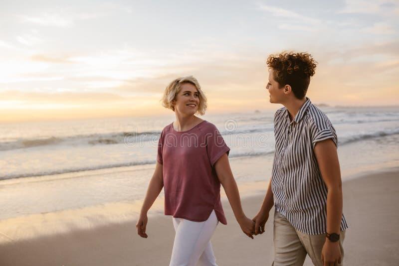 Uśmiechnięty lesbian pary odprowadzenie wzdłuż plaży przy zmierzchem obrazy royalty free