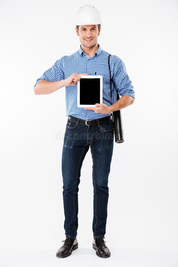 Uśmiechnięty mężczyzna architekt trzyma pustego ekranu pastylkę w budynku hełmie obraz stock