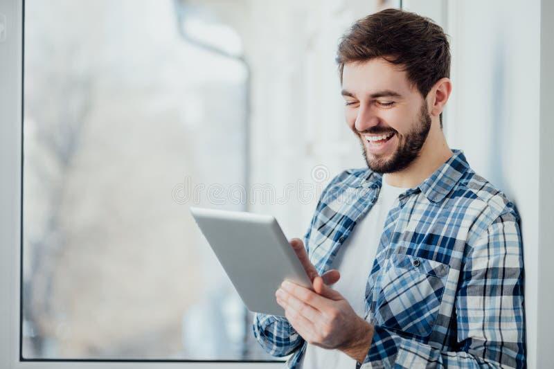 Uśmiechnięty mężczyzna bawić się na cyfrowej pastylce obraz stock