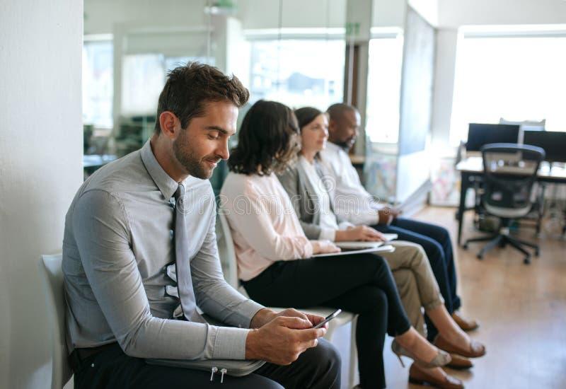 Uśmiechnięty mężczyzna czyta tekst podczas gdy czekać na jego wywiad zdjęcie royalty free