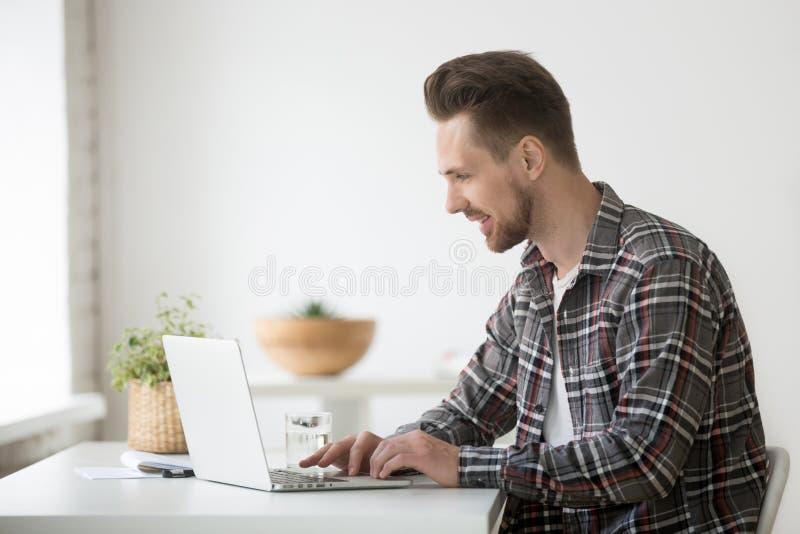 Uśmiechnięty mężczyzna freelancer pracuje na laptopie komunikuje online my obraz stock
