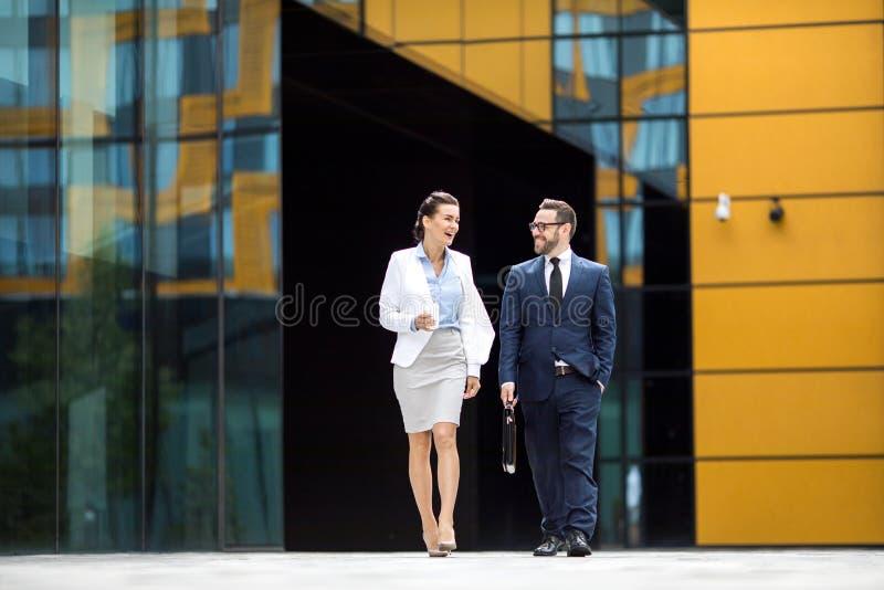 Uśmiechnięty mężczyzna i kobieta dostaje out budynek biurowego obraz royalty free