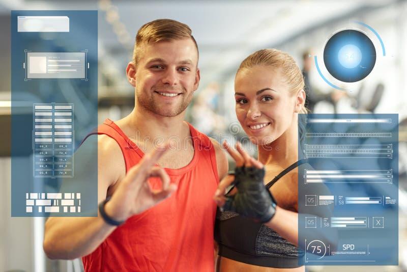 Uśmiechnięty mężczyzna i kobieta pokazuje ok rękę podpisujemy wewnątrz gym fotografia royalty free
