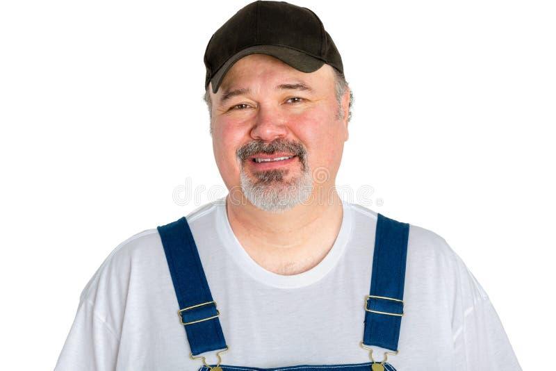 Uśmiechnięty mężczyzna jest ubranym nakrętkę z dungarees zdjęcie royalty free