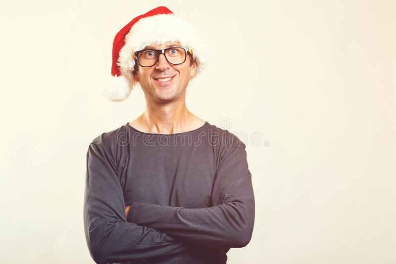 Uśmiechnięty mężczyzna jest ubranym Santa kapelusz w szkłach szczęśliwego nowego roku, Święta tła blisko czerwony czasu Śmieszny  obraz royalty free