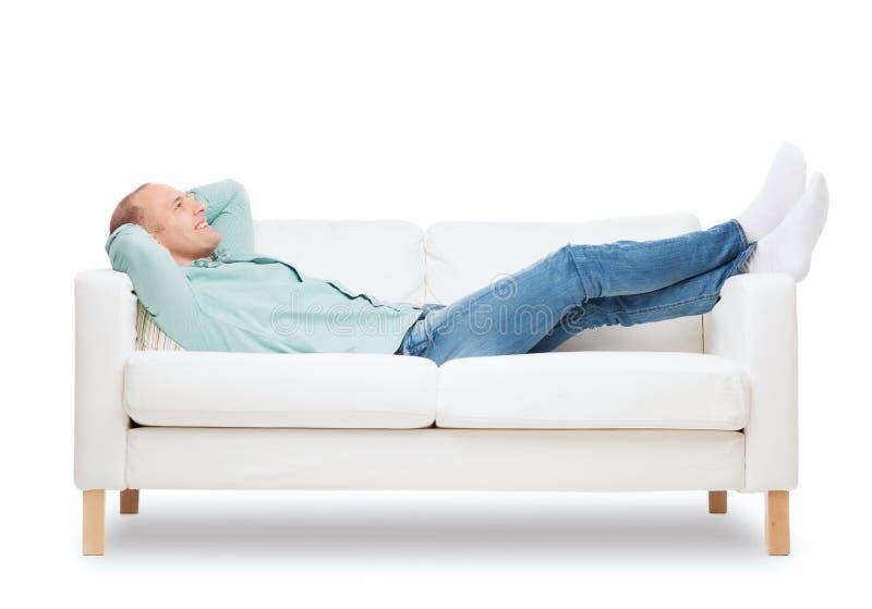 Uśmiechnięty mężczyzna lying on the beach na kanapie zdjęcie royalty free