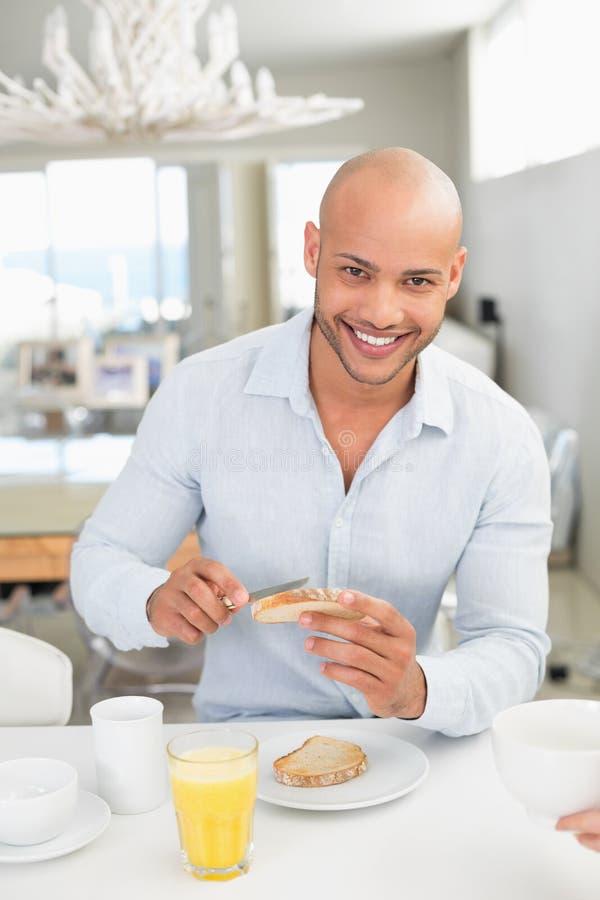 Uśmiechnięty mężczyzna ma śniadanie w domu obrazy stock