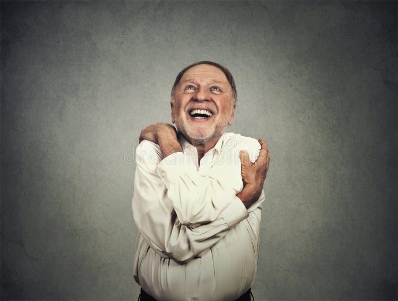 Uśmiechnięty mężczyzna mienia przytulenie himself zdjęcia royalty free