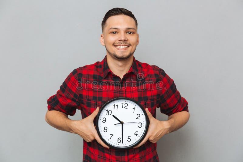 Uśmiechnięty mężczyzna mienia zegar w rękach zdjęcia royalty free
