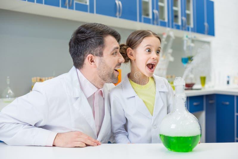 Uśmiechnięty mężczyzna nauczyciel patrzeje z podnieceniem dziewczyna ucznia podczas eksperymentu w lab zdjęcie stock