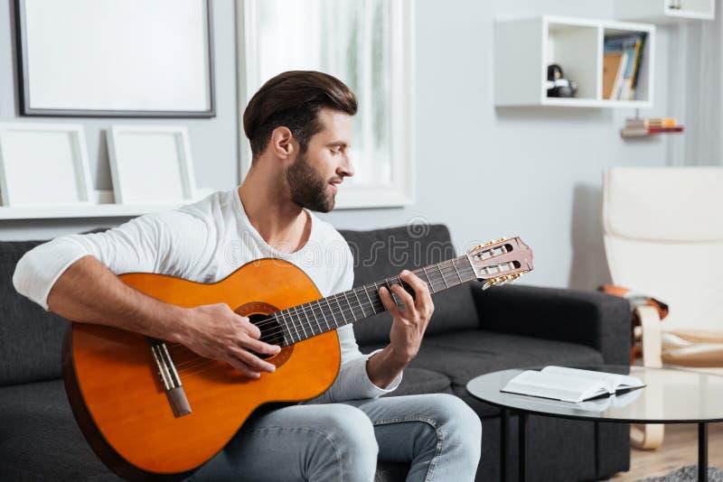 Uśmiechnięty mężczyzna obsiadanie na kanapie bawić się na gitarze fotografia royalty free