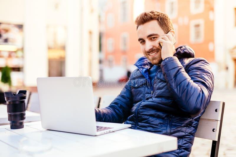 uśmiechnięty mężczyzna opowiada na telefonie komórkowym podczas gdy pracujący od za obrazy stock