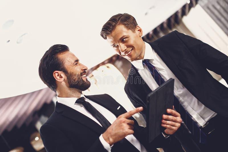 UÅ›miechniÄ™ty mężczyzna patrzÄ…cy na swojego partnera biznesowego stojÄ…cego przy nowoczesnym urzÄ…dzeniu zdjęcie royalty free
