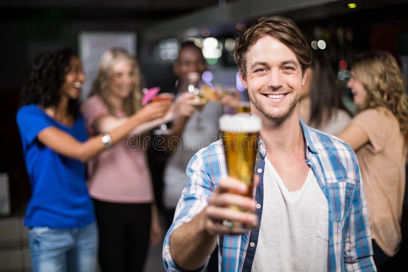 Uśmiechnięty mężczyzna pokazuje piwo z jego przyjaciółmi fotografia royalty free