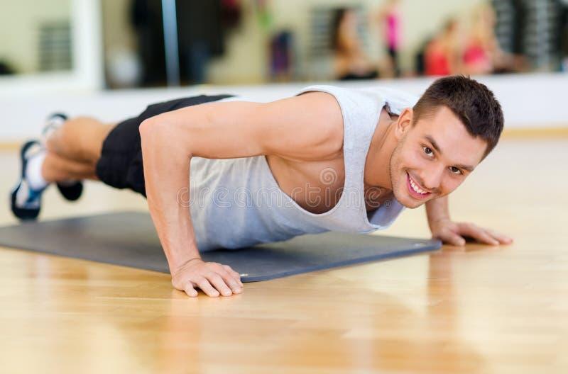 Uśmiechnięty mężczyzna robi Ups w gym zdjęcie stock
