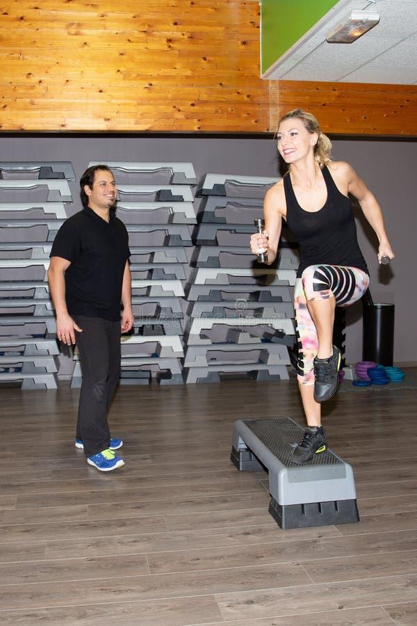 Uśmiechnięty mężczyzna sprawności fizycznej trenera instruktor w gym z blondynki dysponowaną sporty kobietą zdjęcia stock