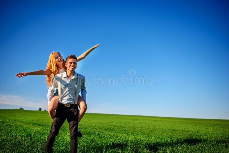 Uśmiechnięty mężczyzna trzyma dalej jego plecy szczęśliwa kobieta która ciągnie out go, zdjęcia royalty free