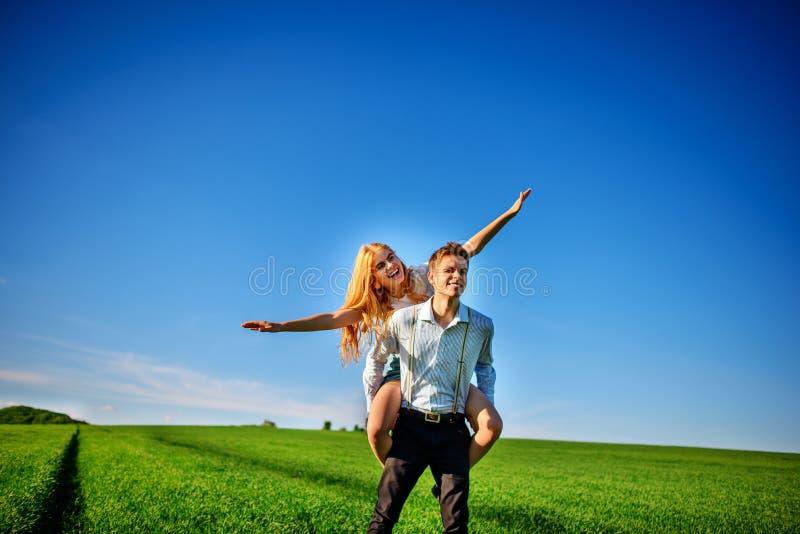 Uśmiechnięty mężczyzna trzyma dalej jego plecy szczęśliwa kobieta która ciągnie out go, obrazy stock